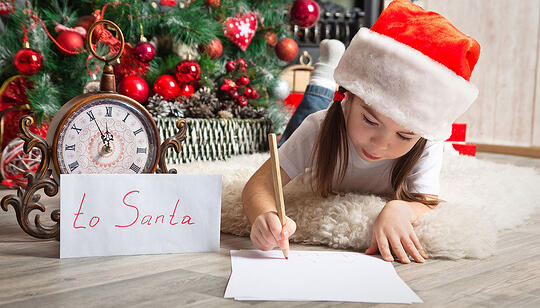 Little Girl Writing Letter to Santa in Front of Christmas Tree